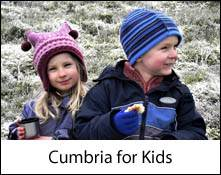 image of two laughing children on an icy lake district hillside which is an image link to the places to visit in the lake district for kids page