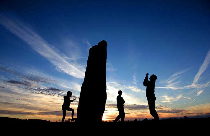 image of people against the sunset at long meg and her daughters stone circle in cumbria, england