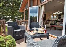 an image of outdoor armchairs and table on decking at calthwaite hall lodges