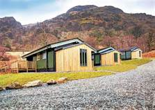 an image of wooden holiday cabins and mountains at hartsop fold Lake District lodges in patterdale holiday park in the lake district