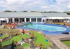 an image of families playing in the outdoor swimming pool and childrens' play area at lakeland leisure park at grange over sands in cumbria