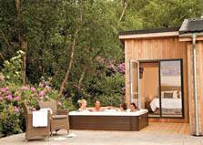 an image of a couple in a hot tub and lake district holiday lodges at north lakes lodges in cumbria
