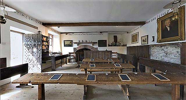 image of old desks and benches in the interior of hawkshead old grammar school.