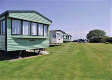 an image of static caravans on grass at rowanbank holiday park at silloth in cumbria