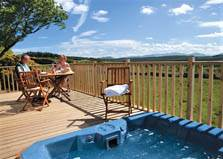 an image of a couple relaxing on the decking beside the private hot tub at their Lake District lodge at thanet wells holiday park at greystoke in cumbria