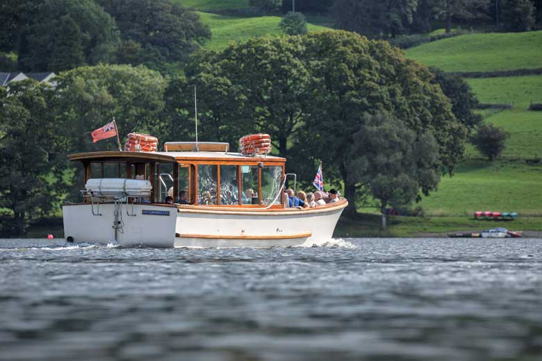 image of Coniston Launch with green fields and trees behind, on Coniston Water in the Lake District