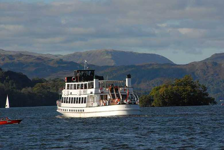 image of a tourist cruise boat on Windermere lake in the South Lakes with the Lake District fells behind