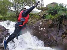 image of a boy jumping into a mountain stream, one of the most popular windermere activities in the Lake District