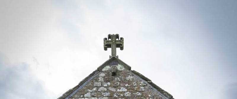 image of a stone head, possibly pagan, on St Mary's Church, Gilcrux