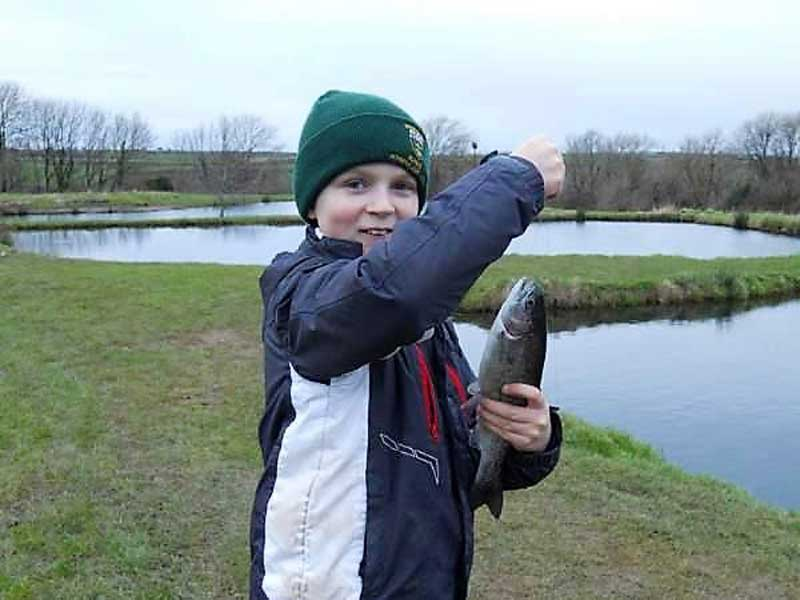 image of a boy with a fish at Gilcrux Trout Fishing Ponds in Cumbria