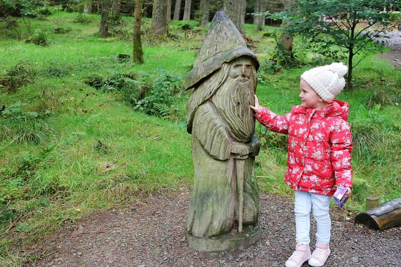 image of a little girl looking at a forest sculpture of a gnome in Whinlatter Forest in the Lake District