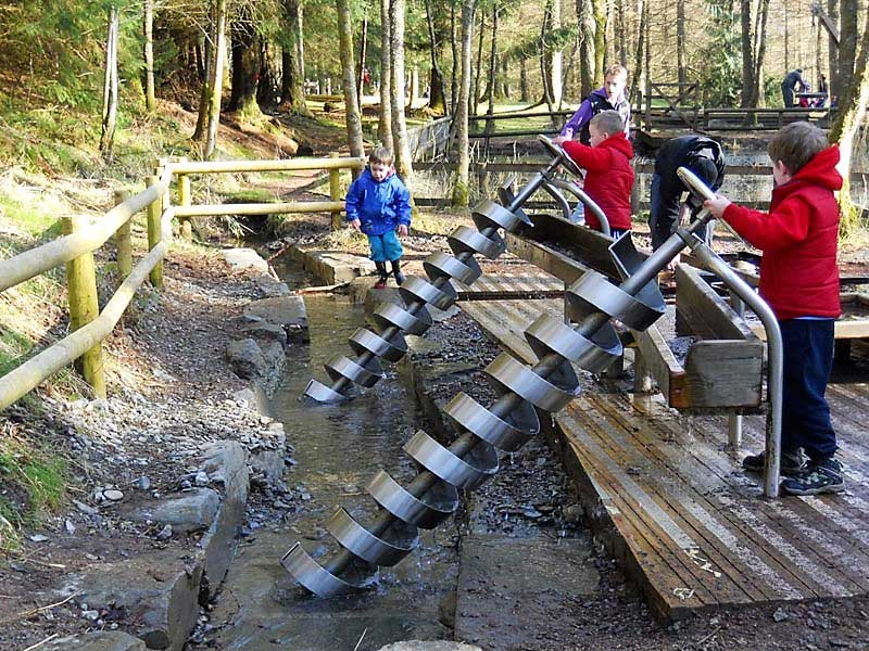 image of children using Archimedes Screw play equipment at Whinlatter Visitor Centre Wildplay area in the Lake District