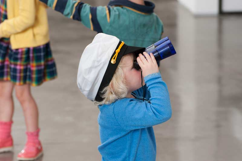 image of a child looking through binoculars at a Windermere Jetty event in the Lake District