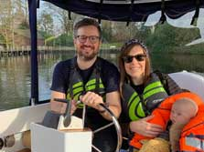 image of a couple and a baby in a windermere boat hire electric boat