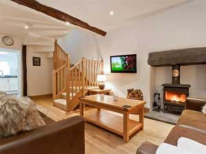 image of the sitting room, with roaring logburner, in a romantic Lake District cottage for two