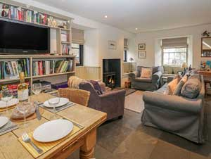image of the open plan sitting room at an Ambleside pet friendly cottage in the Lake District, showing wood burning stove, table set for dinner, sofas and library shelves full of books