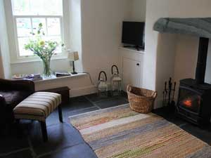 image of a small sitting room at with woodburner and rug, with a vase of flowers in the window, in a holiday cottage in the Lake District