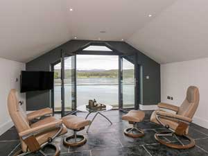 image of two modern chairs and a large window overlooking Windermere lake