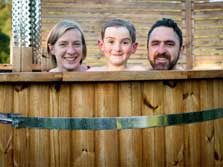 image of a family in a wood fired hot tub at Coniston glamping yurts in the Lake District