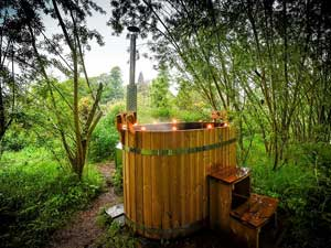 image of a wood fired hot tub in the trees in the Lake District