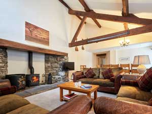image of the sitting room in a large holiday cottage in the Lake District. A spacious but cosy room with woodburning stove, wooden beams and soft sofas. Pet friendly.