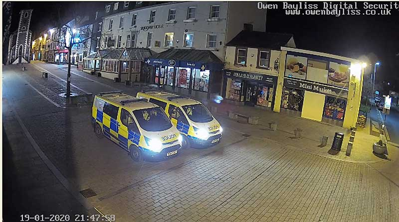 image of a screenshot taken from the webcam in Keswick of two police vans parked up in the Keswick Market Square
