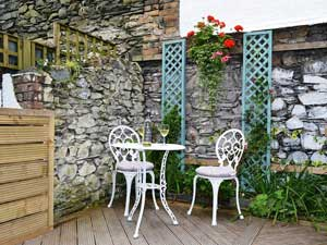 image of two white chairs and a table in the courtyard of a romantic cottage for two in the Lake District
