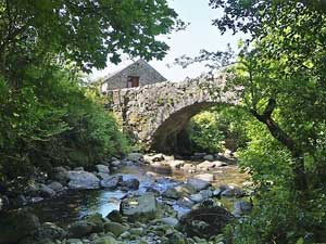 image of a small romantic Lake District cottage for two beside a packhorse bridge and trees