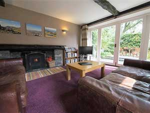 image of leather sofas and woodburning stove in a luxury pet friendly cottage in the Lake District. Views through the large glass doors show the Lakeland landscape outside.