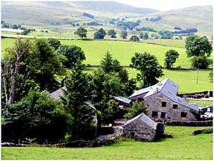 image of a Lake District cottage set in rolling green fields