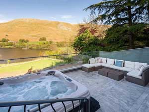 image of a luxury cottage with hot tub in the Lake District with views from the deck over Ullswater lake