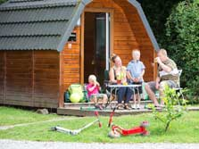 image of a family sitting outside a Glamping Lake District pod