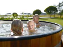 image of a family in a wood fired Hot Tub at a Lake District Glamping site