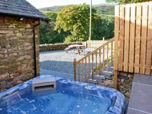 image of an outdoor hot tub and fields behind a luxury pet friendly cottage in the Lake District
