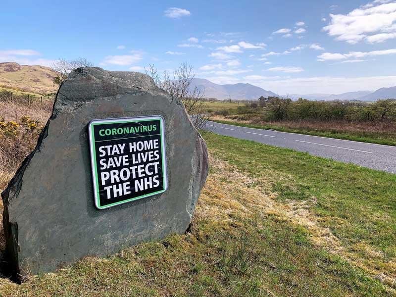 image of a sign urging visitors to stay home, save lives, protect the NHS covering the Lake District National Park sign at the entrance to the park during the covid-19 coronavirus crisis in Cumbria April 2020