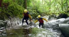 image of two people ghyll scrambling in a Lake District stream running through a forest