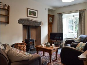 image of the interior of a holiday cottage in the Lake District with a woodburner and leather armchairs.