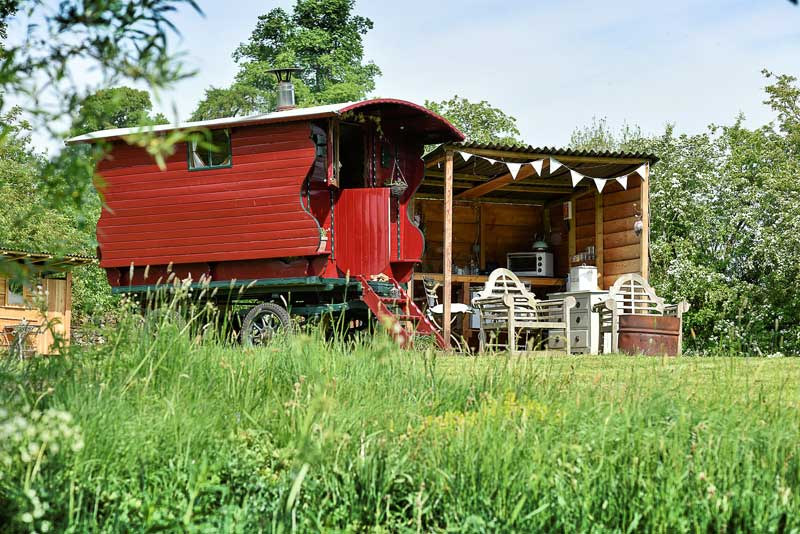 image of a red Lake District staycation shepherd's wagon in a field with trees behind