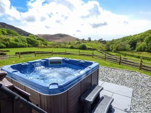 image of a hot tub with the southern Lake District fells behind at a holiday cottage
